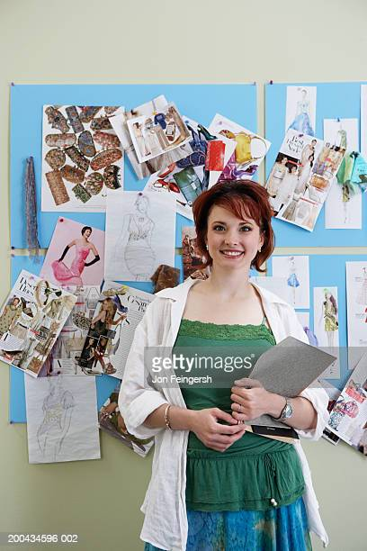 Clothing designer in front of sketches, portrait