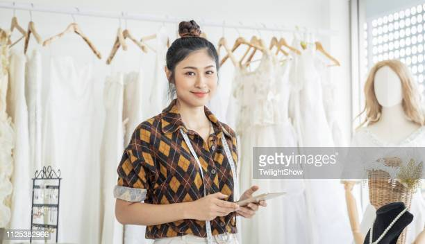 clothing designer woman working in her small business office - long dress stock pictures, royalty-free photos & images