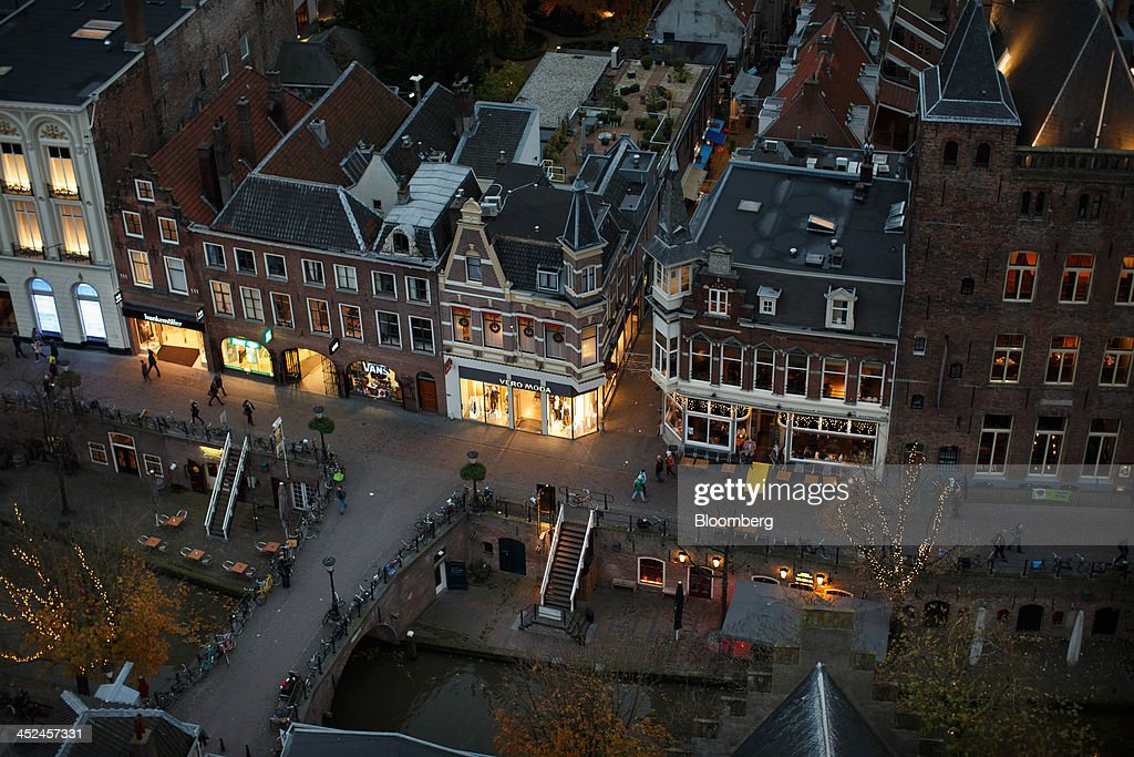 Clothing fashion retailers and a cafe sit along a canal in Utrecht, Netherlands, on Thursday, Nov. 28, 2013. European government bonds were little changed as investors showed a muted reaction to Standard & Poor's decision to raise its outlook on Spain's debt and strip the Netherlands of its top credit rating. Photographer: Jasper Juinen/Bloomberg via Getty Images
