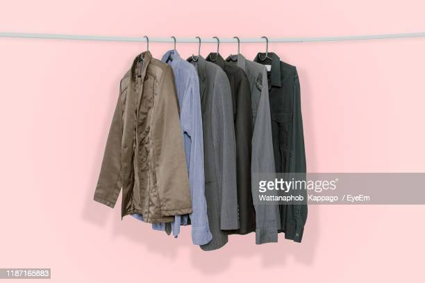 clothing hanging against pink background - 収納ラック ストックフォトと画像