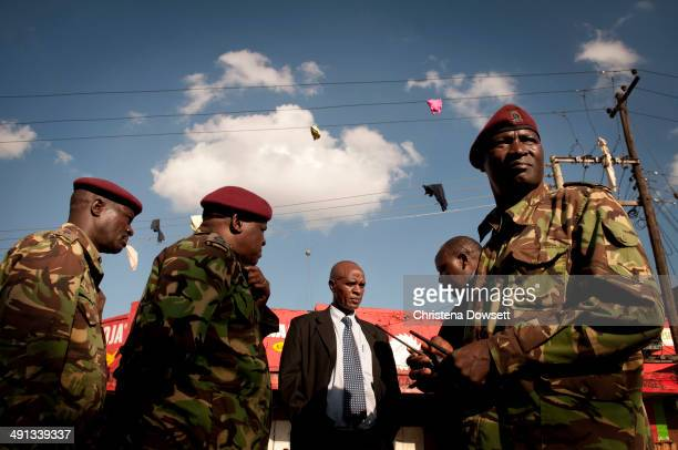 Clothing hangs from a power line as members of Kenya's General Service Unit discuss two improvised explosive devices which went off in Gikomba market...