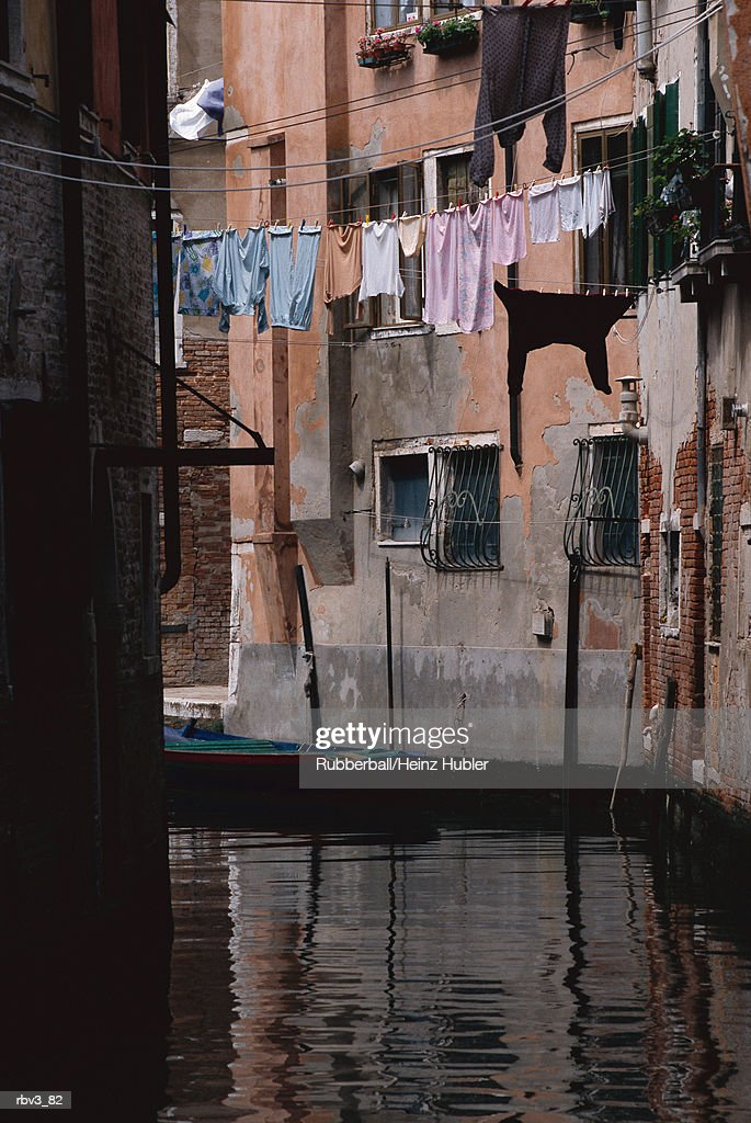 clothing hangs from clothes lines hanging from beige buildings above dark canal water : Foto de stock