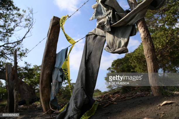 TOPSHOT Clothing is seen on March 19 2017 around a mass grave where 12 bodies were exhumed Friday by the authorities in El Arbolillo village in...