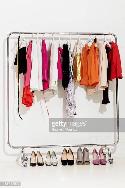 Clothing rail with pairs of footwear on white bakcground