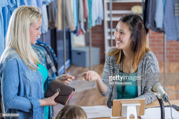 Clothing store employee accepts customer's credit or loyalty card