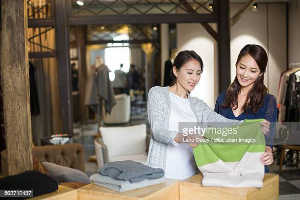 Clothing store owner helping customer with choosing clothing