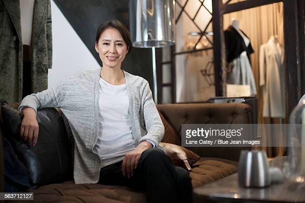 clothing store owner sitting on sofa - デザイナー服 ストックフォトと画像
