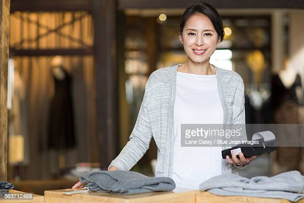 clothing store owner with credit card reader - asian 50 to 55 years old woman stock photos and pictures