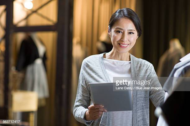 clothing store owner with digital tablet - デザイナー服 ストックフォトと画像