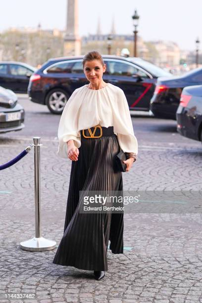 Clotilde Courau wears a white flowing large sleeves blouse a large black Valentino belt a black leather large pleated skirt a black clutch black...