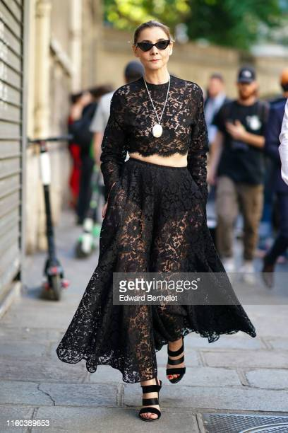 Clotilde Courau wears sunglasses, a cropped lace mesh embroidered black dress, a long necklace, outside Valentino, during Paris Fashion Week -Haute...