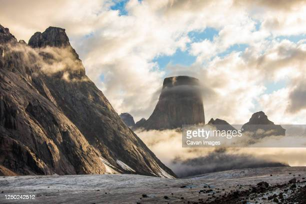 cloud circles mount asgard, auyuittuq national park, baffin island. - baffin island stock pictures, royalty-free photos & images