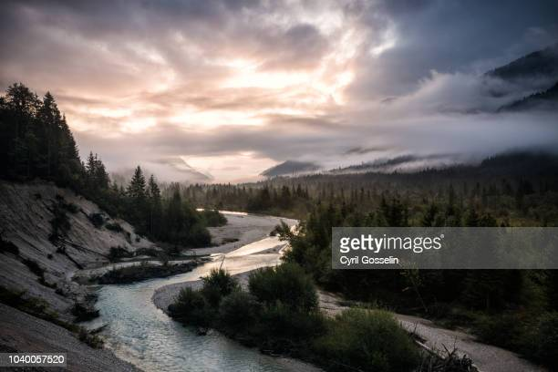 cloud covered sky over the isar at sunrise in autumn - lenggries stock pictures, royalty-free photos & images