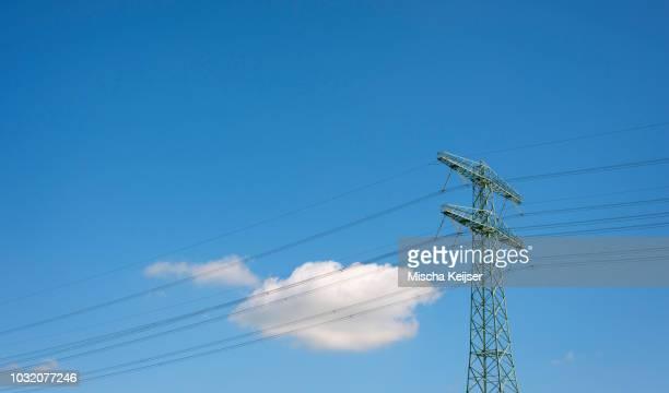 Cloud floating behind power pylon