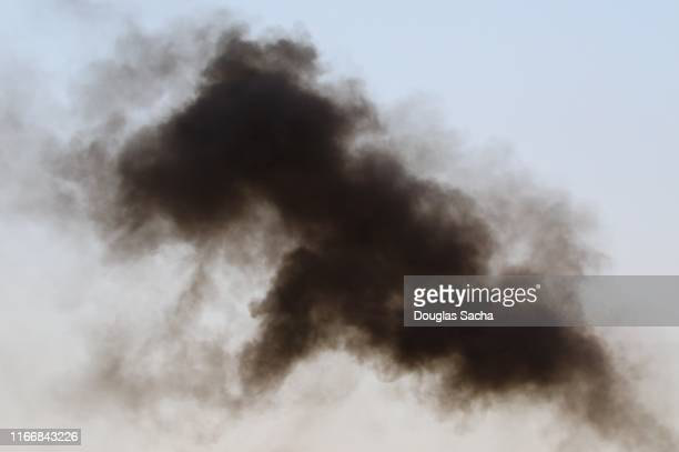 cloud of black smoke rising in the air - thick stock pictures, royalty-free photos & images
