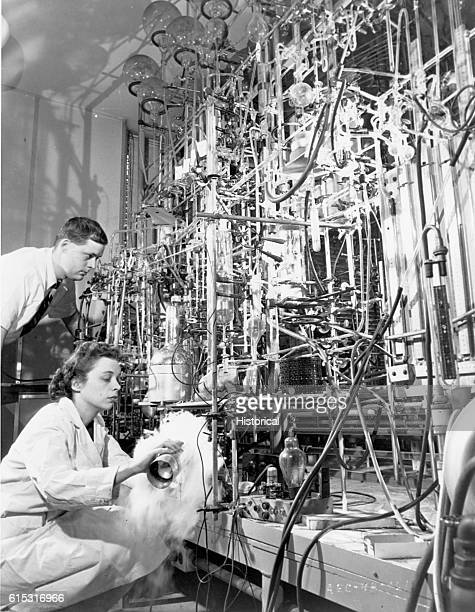 A cloud of condensed air forms at the base of a maze of glass tubing that towers over two scientists as they use radioisotopes and liquid nitrogen to...