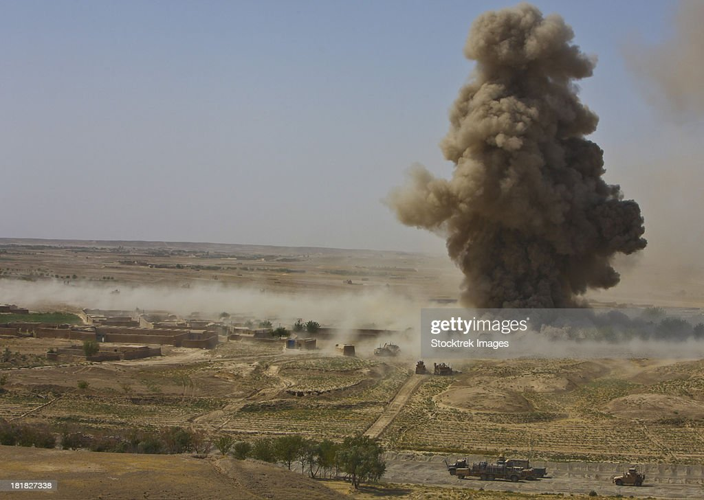 A cloud of dust and debris rises into the air in Afghanistan. : Stock Photo