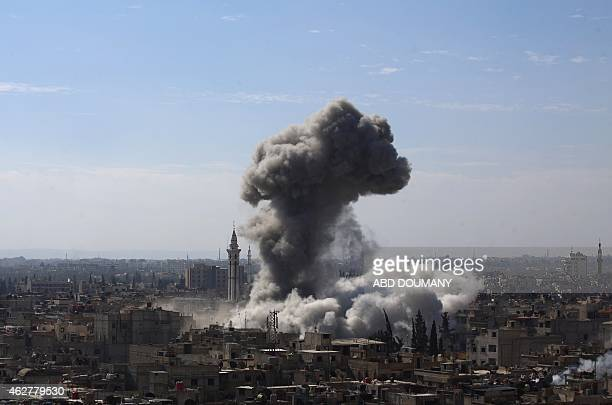 Cloud of smoke rises following an air strike by Syrian government forces in the rebel-held area of Douma, north east of the capital Damascus, on...