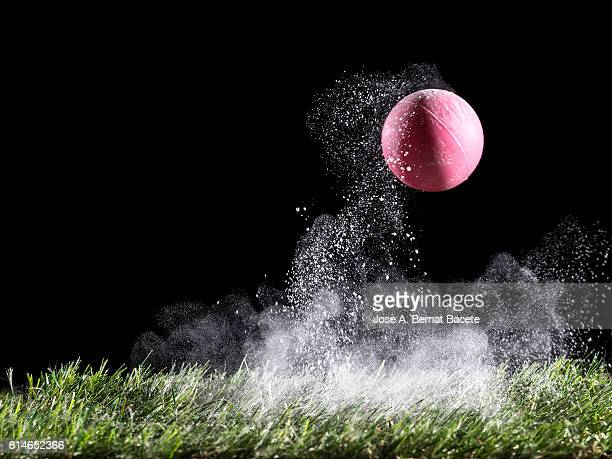 Cloud of white powder produced by the impact of a ball on the lawn of grass