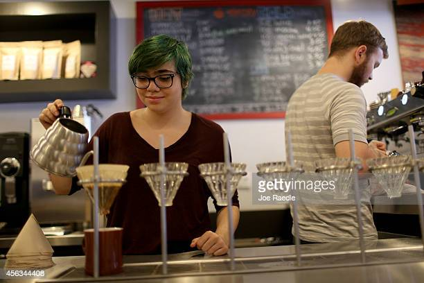 Cloud Perez Vento pours a slowbrew process coffee and Mike Rodriguez makes an espresso at Eternity Coffee Roasters during National Coffee Day on...