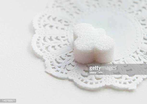 A cloud shaped sugar cube on a lace doily