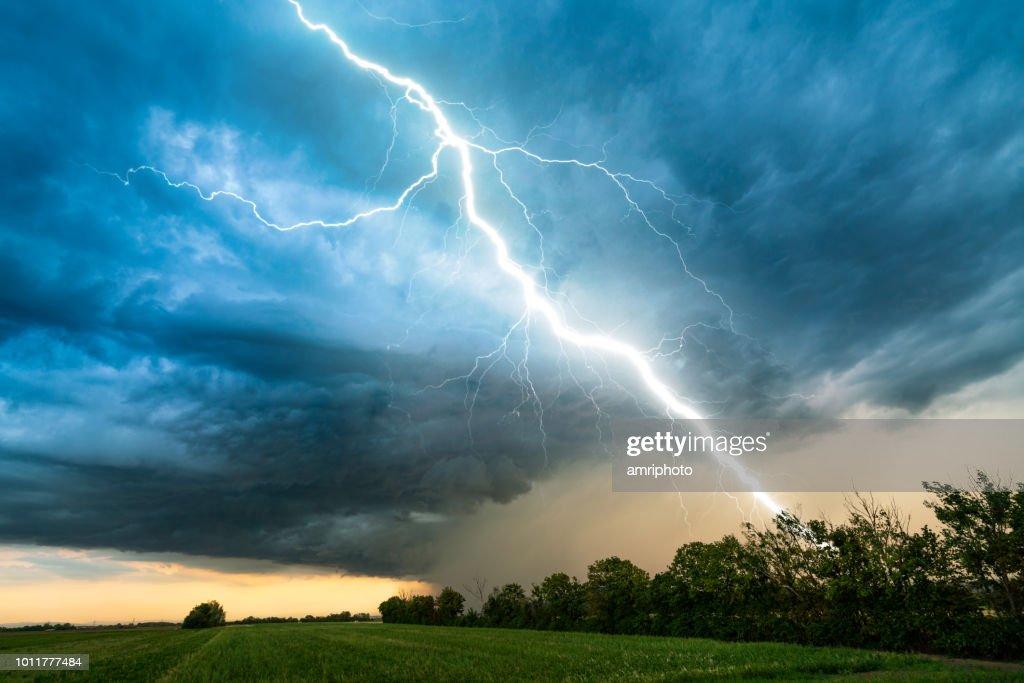 cielo nuvoloso tempesta con fulmine sul paesaggio rurale : Foto stock