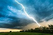 cloud storm sky with thunderbolt over rural landscape