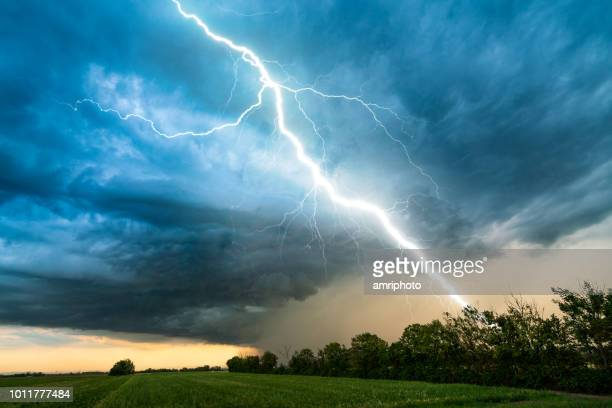 cloud storm sky with thunderbolt over rural landscape - storm stock pictures, royalty-free photos & images