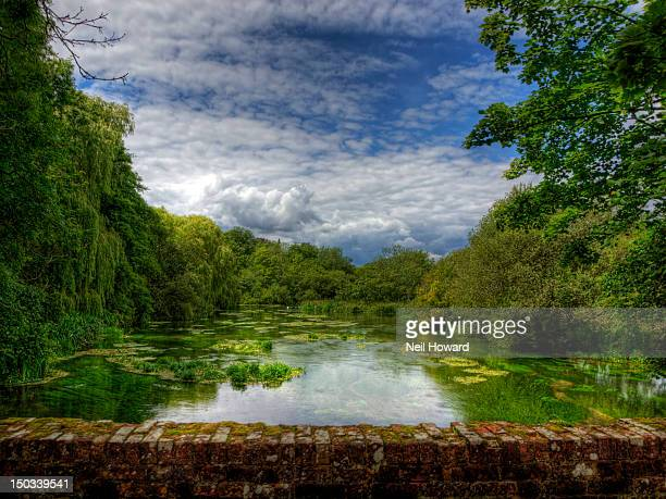 cloud studded sky reflected in treed river - winchester hampshire stock photos and pictures
