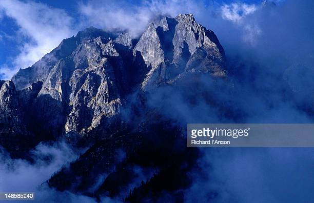 cloud swirling around the jagged escarpment in the valley below the village of temang (2600m) on the annapurna circuit trek. - escarpment stock pictures, royalty-free photos & images