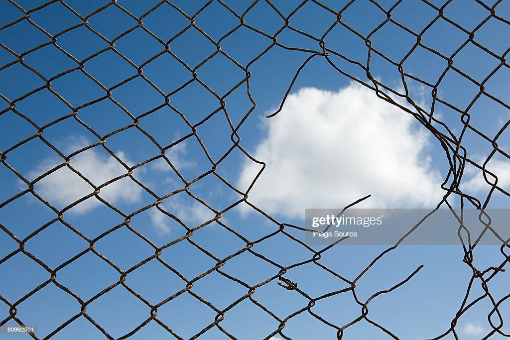 Cloud through a broken fence : Stock Photo