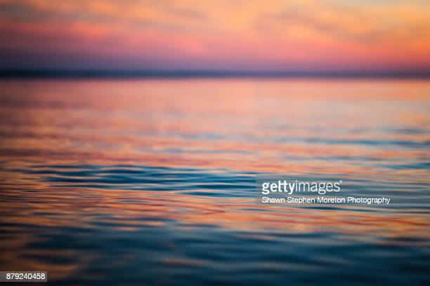 cloud typologies - the pastel color sunset sky reflects on the surface of the canadian lake - standing water stock pictures, royalty-free photos & images