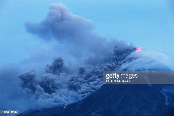 TOPSHOT Cloudcovered Mayon volcano spews ash as it erupts near the Philippine city of Legazpi in Albay province early on January 16 2018 Thousands...