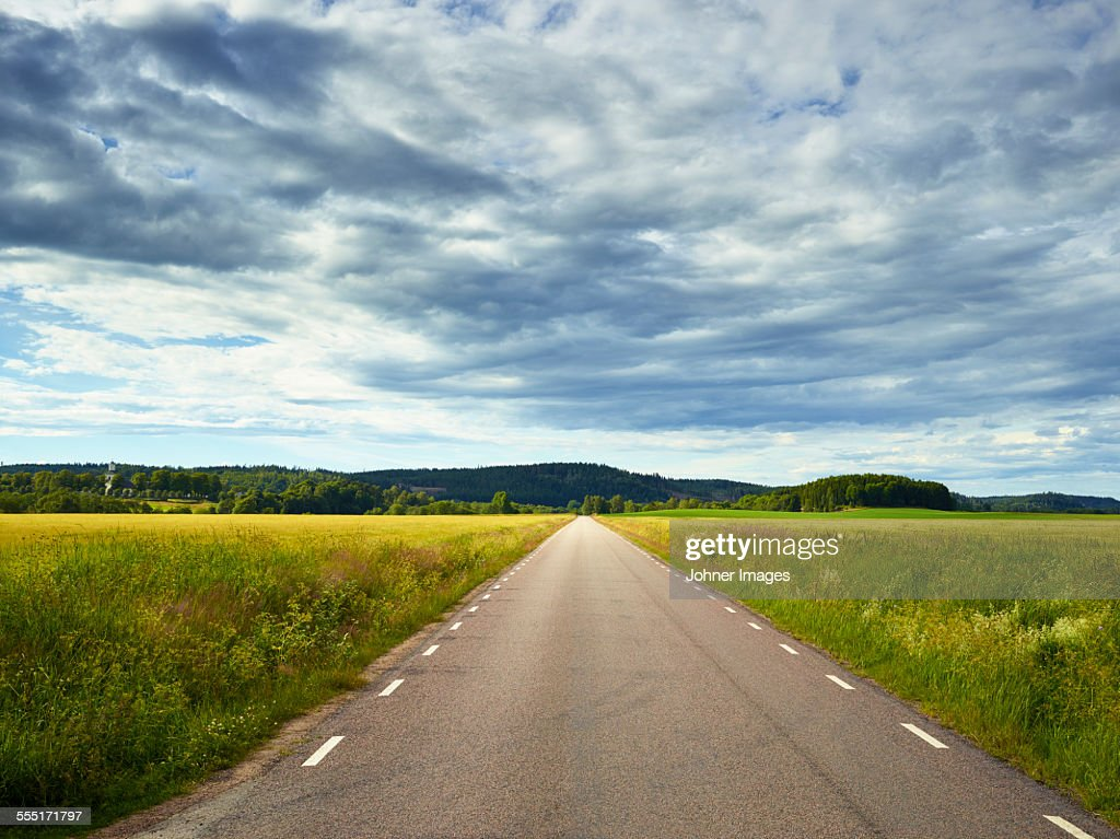 Clouds above country road : Stock Photo