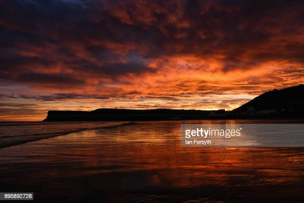 Clouds above Huntcliff and the beach light up with dramatic colours during a winter sunrise on December 20 2017 in SaltburnbytheSea England Milder...