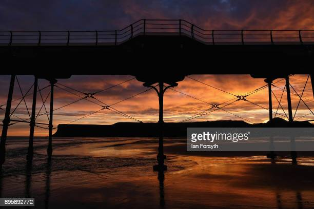 Clouds above Huntcliff and the pier light up with dramatic colours during a winter sunrise on December 20 2017 in SaltburnbytheSea England Milder...