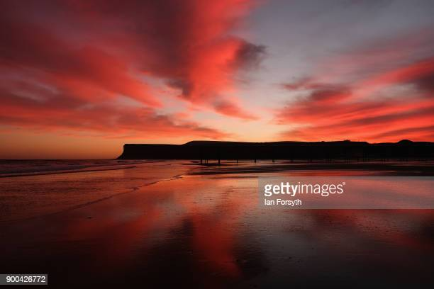 Clouds above the beach and cliffs light up dramatically as the sun rises on January 2 2018 in SaltburnByTheSea England Rain and strong winds are...
