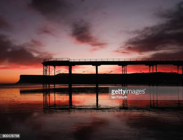 Clouds above the beach pier and cliffs light up dramatically as the sun rises on January 2 2018 in SaltburnByTheSea England Rain and strong winds are...