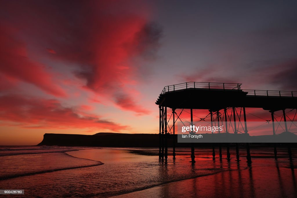 Clouds above the beach, pier and cliffs light up dramatically as the sun rises on January 2, 2018 in Saltburn-By-The-Sea, England. Rain and strong winds are expected to arrive across the country later today with Storm Eleanor set to bring 70-80mph gusts to some parts of the country.