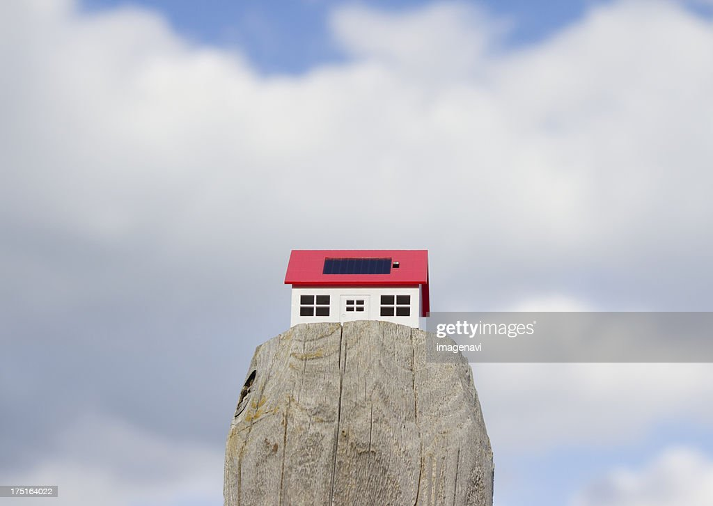 Clouds and a miniature solar home : Stock Photo
