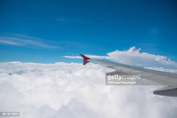 Clouds and skies are seen through the window of a classic plane through the aircraft window to the jet engine, looking through the aircraft window during flight.
