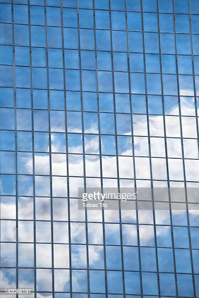 Clouds and sky reflected in mirrored windows of an office building
