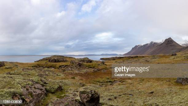clouds and snowy mountain tops near stokksnes, iceland - 荒野 ストックフォトと画像