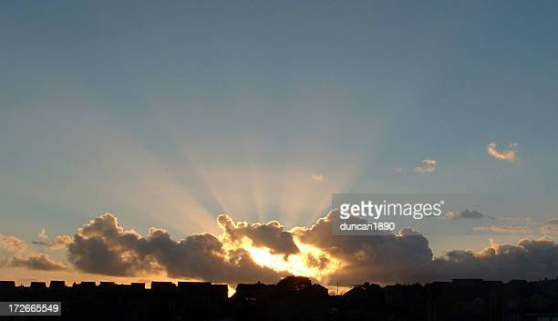 Wolken und Sonne über Häuser