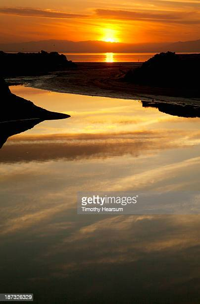 clouds and sun reflected in water at sunset - timothy hearsum imagens e fotografias de stock