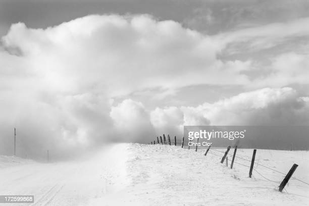 Clouds and wooden fence in snowy landscape