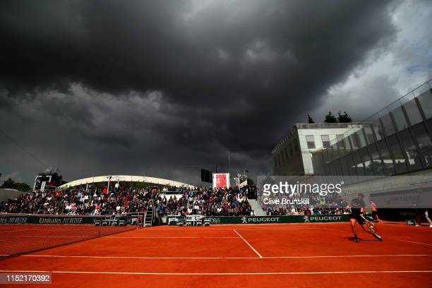 Clouds begin to cover during the during his mens singles first round match against between Cameron Norrie of Great Britain and Elliot Benchetrit of...