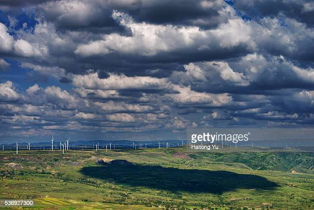 Clouds casting shadows on the grounds of a wind farm