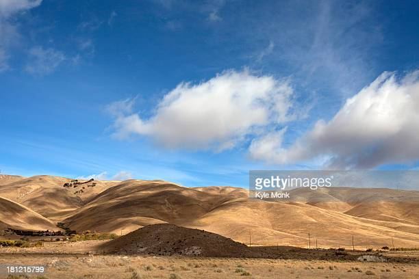 Clouds casting shadows over dry rural landscape