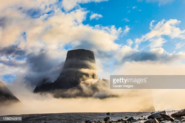 clouds circle mount asgard, baffin island. - canada stock pictures, royalty-free photos & images
